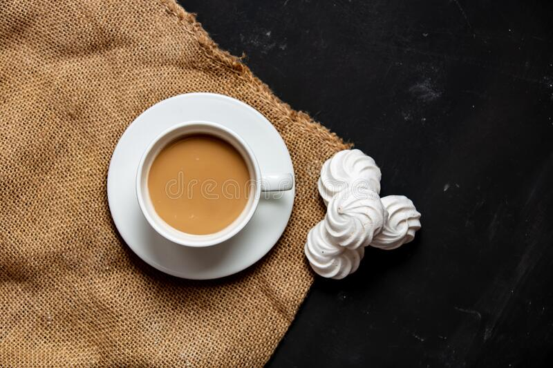 White cup of coffee and meringue on dark background royalty free stock photos