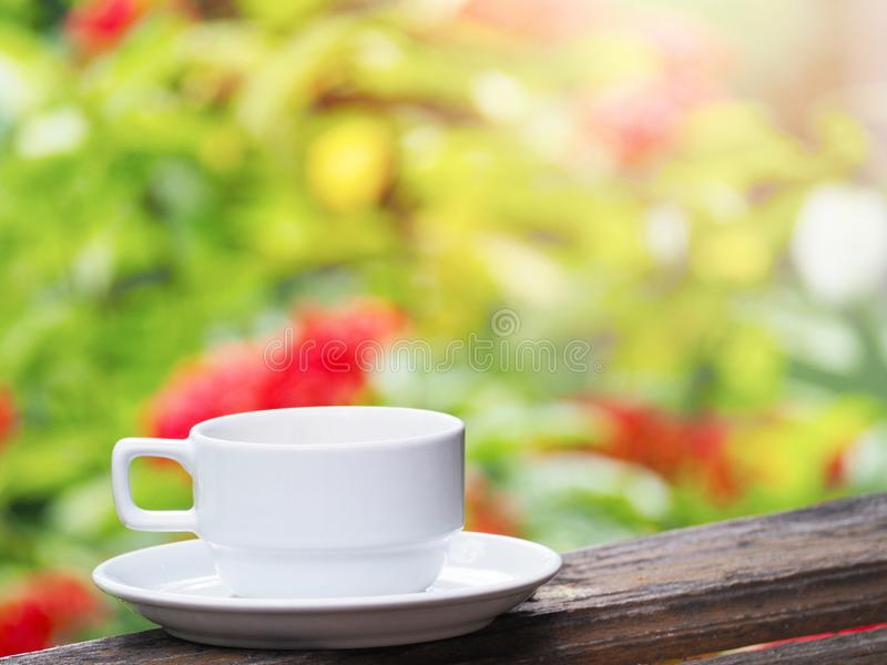 White cup of coffee over green floral abstract blur background stock photography