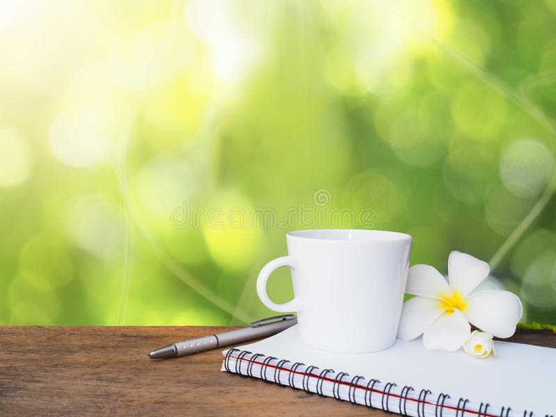 White cup of coffee, pen and notepad on wooden table stock photo