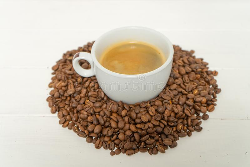 White cup with coffee in the pile of coffee beans on the white wooden background. stock images