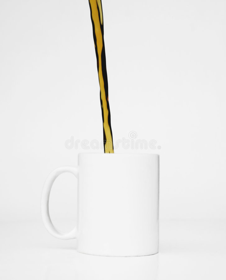 White Cup Coffee Pour. Stream of coffee pours into a white mug against a white background royalty free stock images