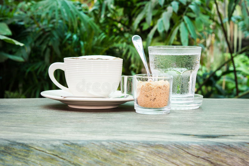 White cup of coffee, water and cane sugar royalty free stock photo