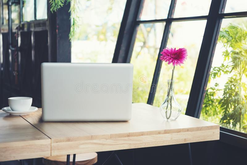 White cup of coffee on the wood desk with laptop and pink flower stock photos