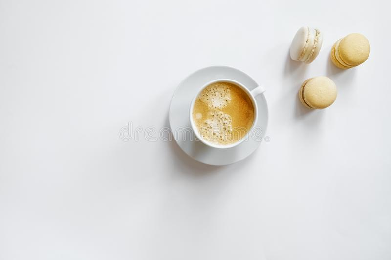 White cup of coffee with yellow macarons. stock photography