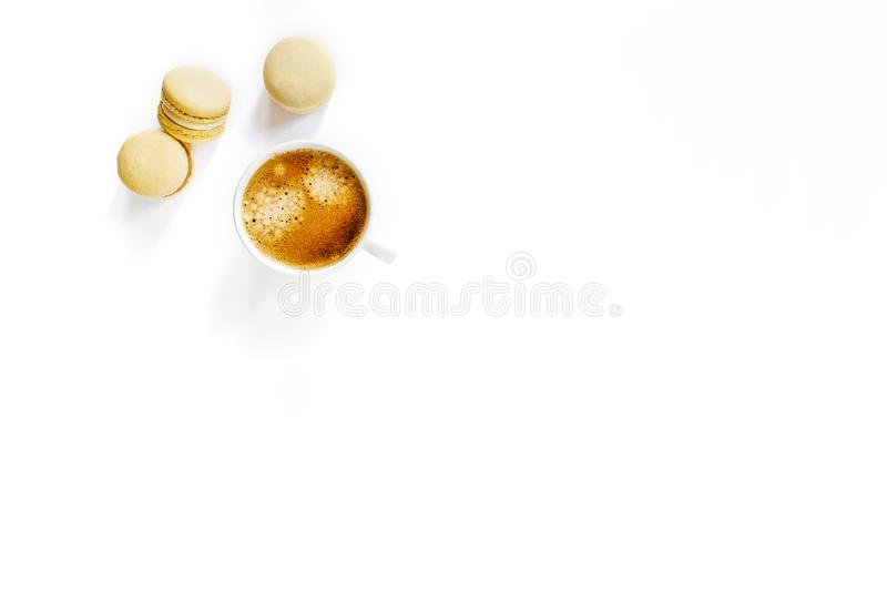 White cup of coffee with yellow macarons. stock image