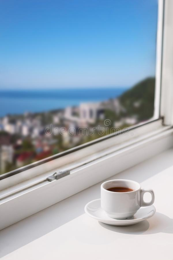 Coffee cup on a window sill. White cup with drink on a window sill with blurred city view with blue sky and sea copy space royalty free stock photo
