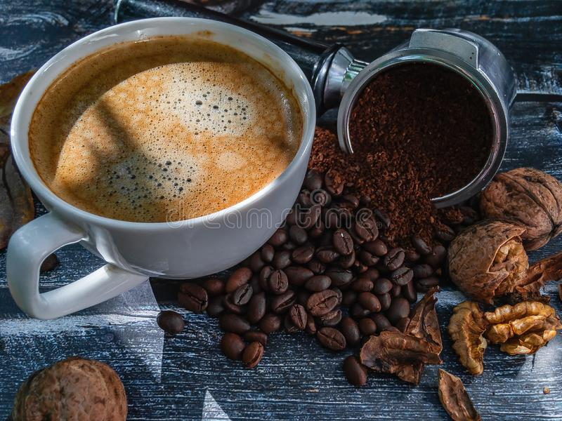 A white cup of espresso surrounded by coffee beans. royalty free stock photos