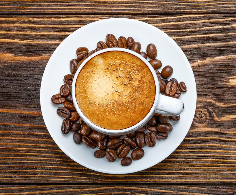 White cup of espresso on a wooden background stock image