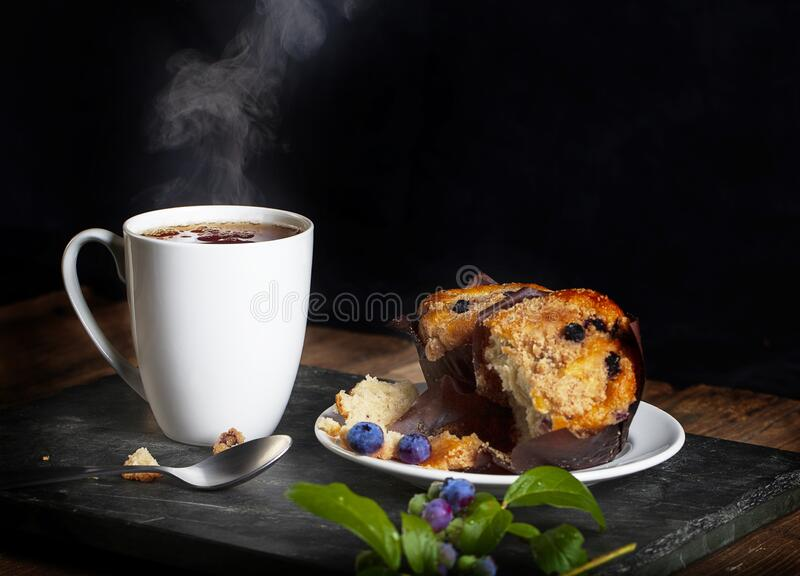 Steaming Hot Drink and Blueberry Muffins stock photos