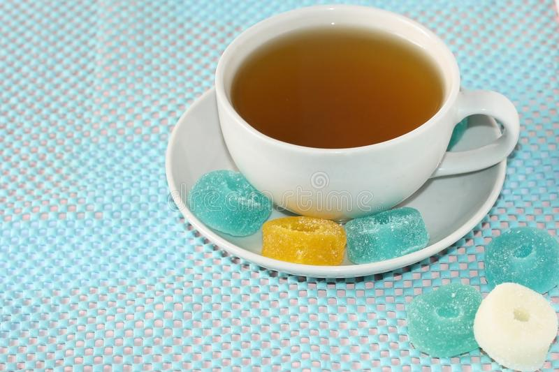 White cup with green tea on a saucer with multi-colored marmalade sweets.Sugar sweet Christmas sweets. Different gelatinous sweet stock image