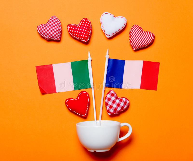 White cup and heart shapes with France nad Italy flags. On orange background stock images