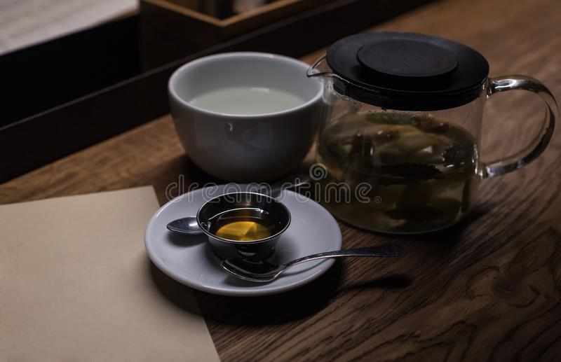 White cup. honey and tea in a scalded teapot. A cup of tasty tea in cafe. White cup for tea, honey and tea in a scalded teapot. Tea drinking accessories. A cup royalty free stock image