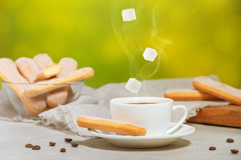 White cup of hot aromatic coffee with steam and falling sugar cubes. Traditional italian savoiardi biscuits or ladyfingers cookies. On a plate and in a glass stock photos