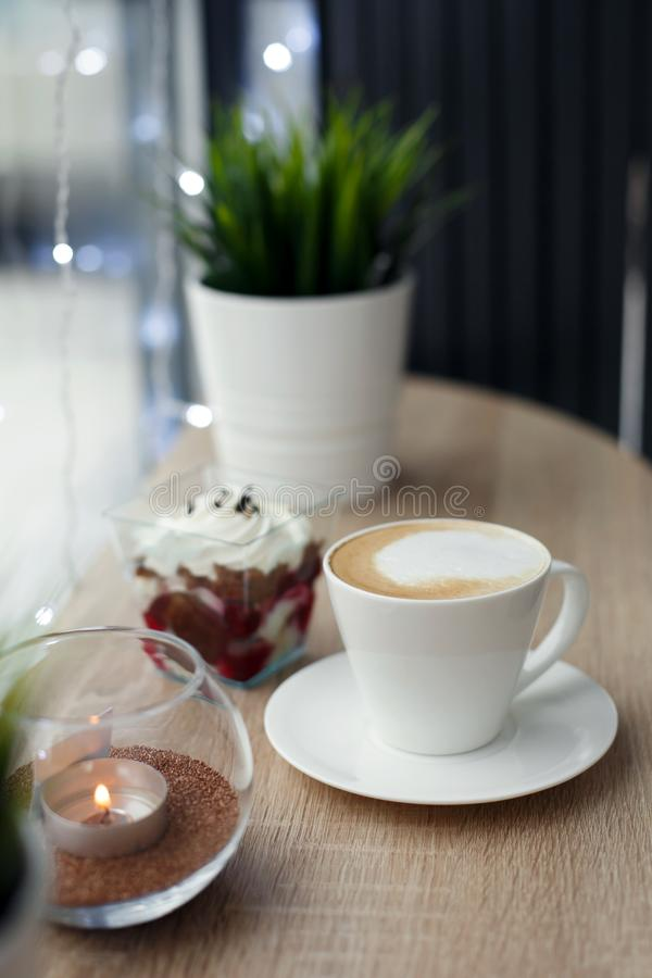 White cup of hot cappuccino on white saucer and red velvet dessert on wooden bar table next to window. Cold snowy weather outside.  royalty free stock images