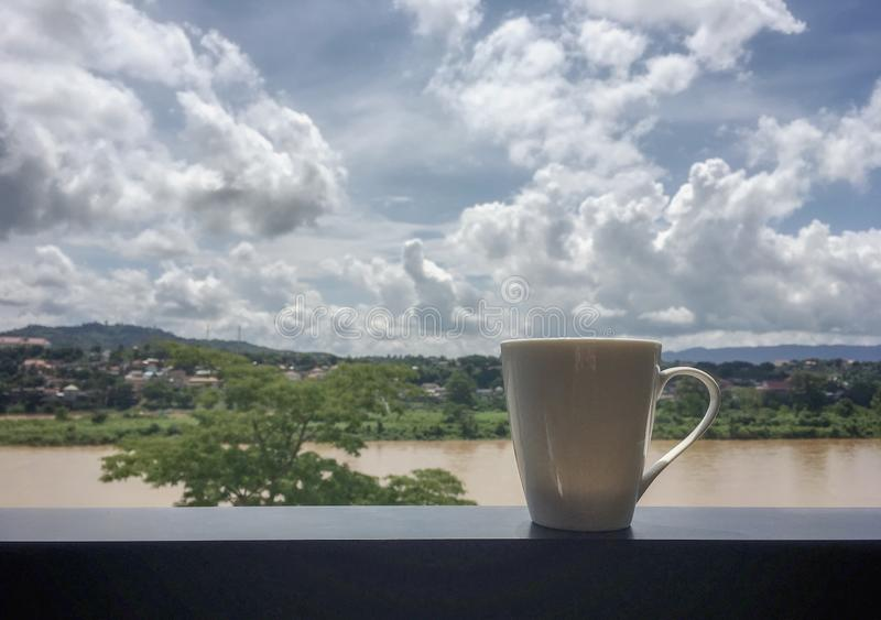 A white cup of hot coffee on terrace in front of big river background royalty free stock images