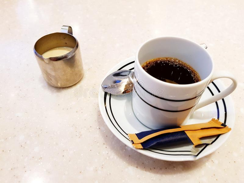 White cup of hot espresso coffee with brown sugar bag, small spoon and milk mug on the marble table with copy space at café shop stock photo
