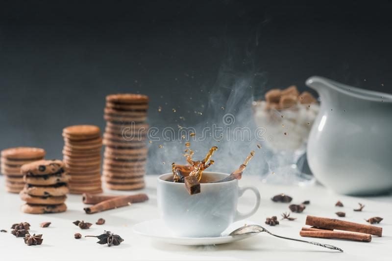 White cup of hot steaming coffee with splashing sugar cubes on table with cookies. And spices royalty free stock image