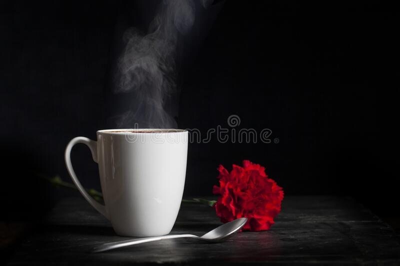 White Cup with Hot Steaming Drink and Flower stock image