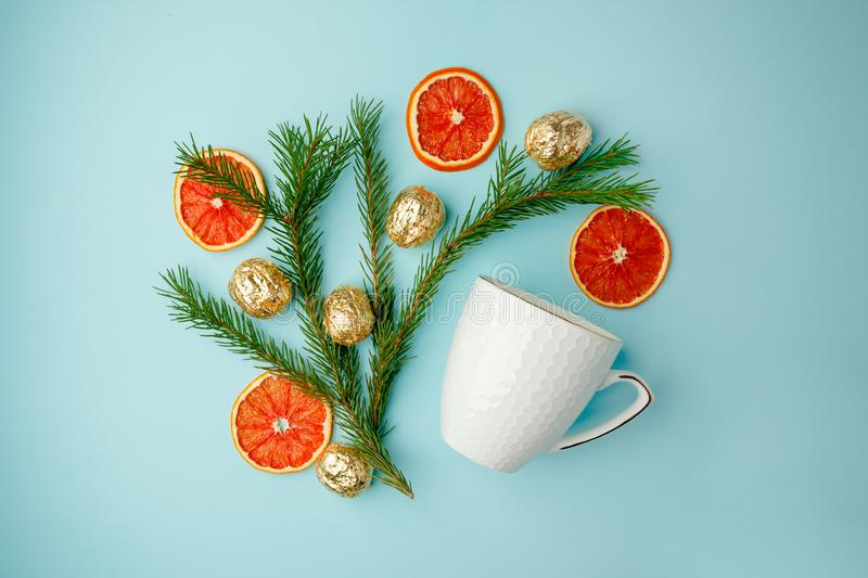 White cup of hot tea with candied orange and xmas decorative things Christmas winter beverage Christmas food concept on blue. Background stock photography