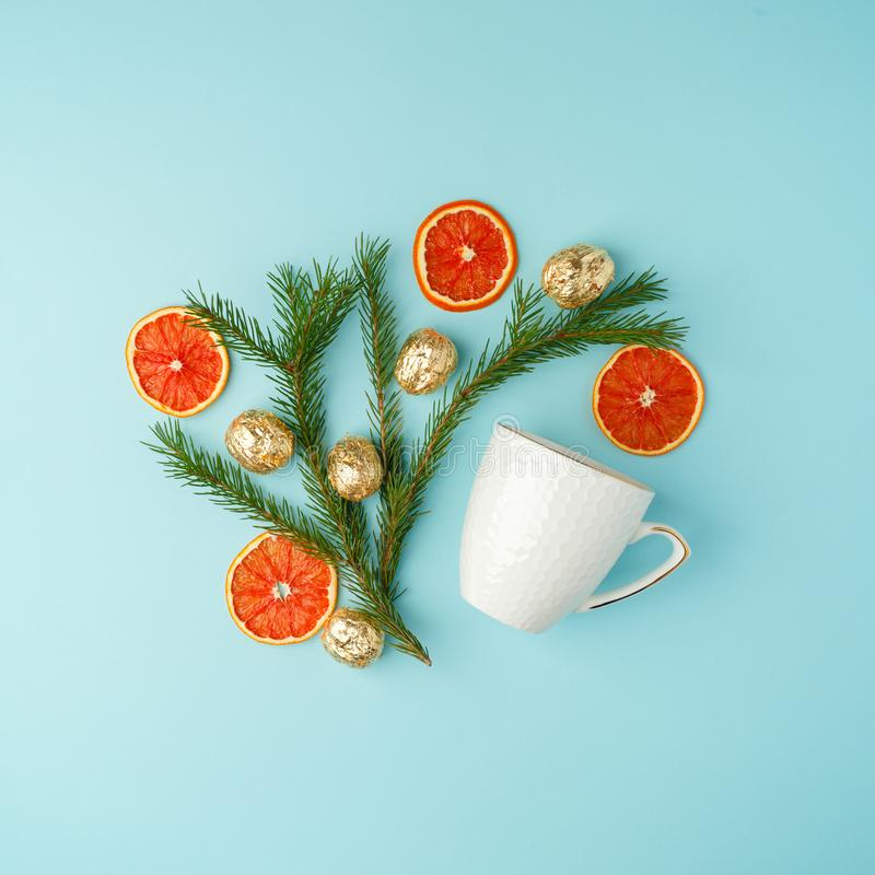 White cup of hot tea with candied orange and xmas decorative things Christmas winter beverage Christmas food concept on blue. Background royalty free stock images