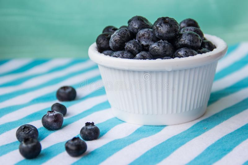 A Cup Of Juicy Blueberries At A Bright Blue Stripy Background. A white cup with juicy blueberries at the stripy blue-and-white background royalty free stock photography