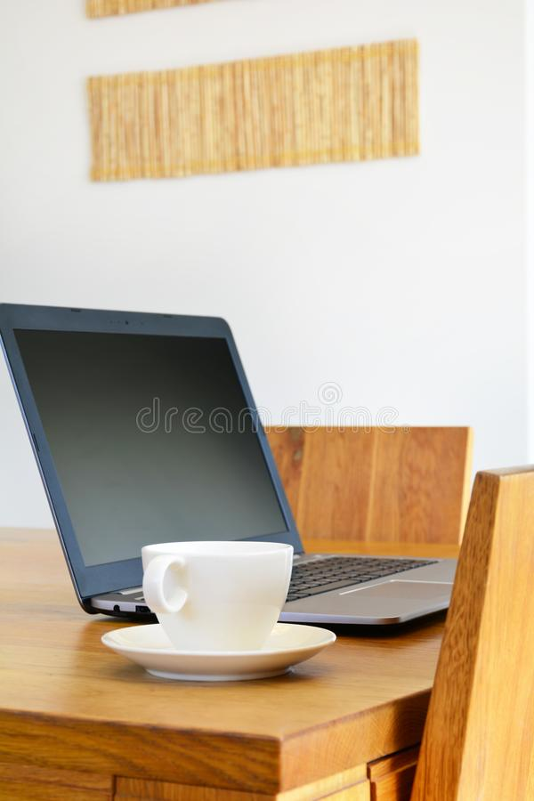 White cup and laptop on natural wood dining table. Remote work c stock photos