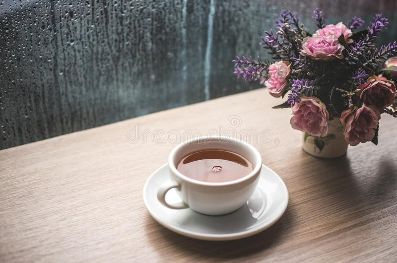A white cup of lemon green tea on wooden table with drop water in rain season. cafe shop with rose flower in pot stock photo
