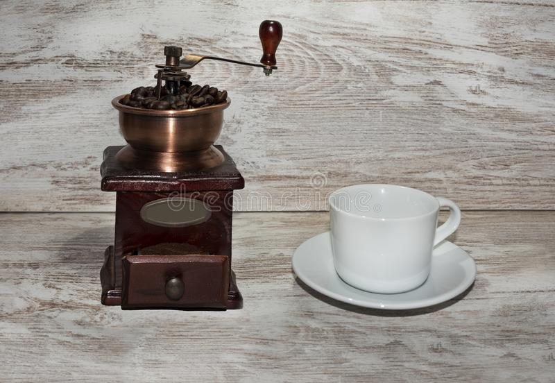 White cup and plate with beans, milling coffee and a wooden grinder on rustic background. With copy space royalty free stock photo