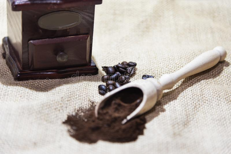 White cup and plate with beans, milling coffee and a wooden grinder on rustic background. With copy space stock images