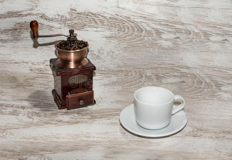White cup and plate with beans, milling coffee and a wooden grinder on rustic background. With copy space stock photography