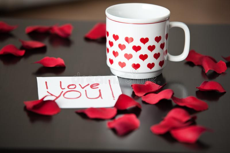 White cup with red hearts and an I-love-you-note on a black table, surrounded by red rose petals. royalty free stock image