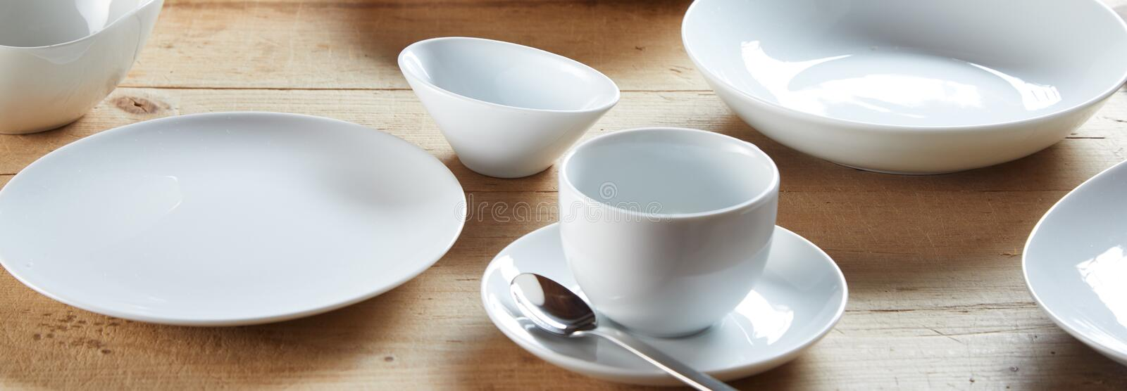 White cup on saucer and ceramic bowls stock images