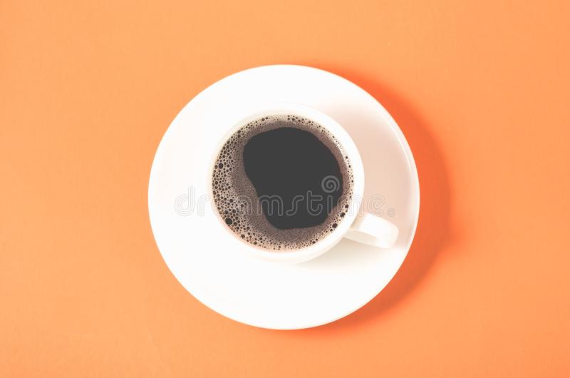 White cup with a saucer on a orange background/white cup of espresso with a foam on a orange background, top view. Coffee full black energy hot drink breakfast royalty free stock images