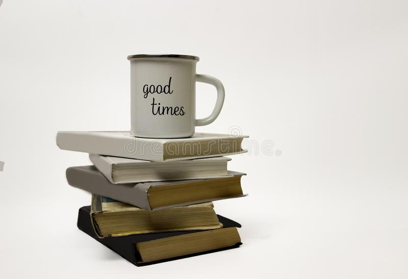 A white cup stands on a pile of books. A stack of books from black to white. The inscription on the cup `good times royalty free stock photography