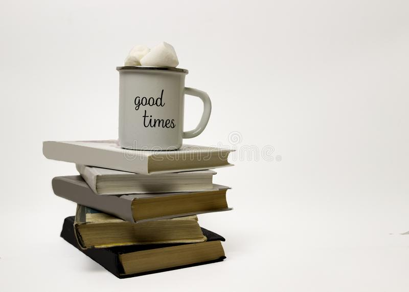 A white cup stands on a pile of books. A stack of books from black to white. The inscription on the cup `good times royalty free stock photos