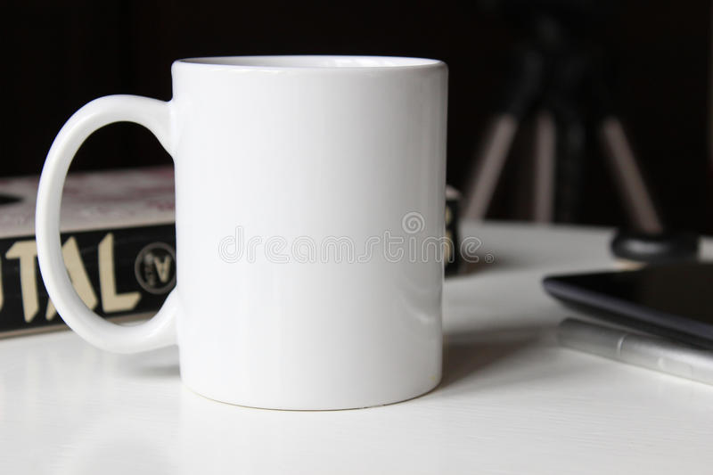 White cup on a table. White cup, mug on a table. Mockup for designs