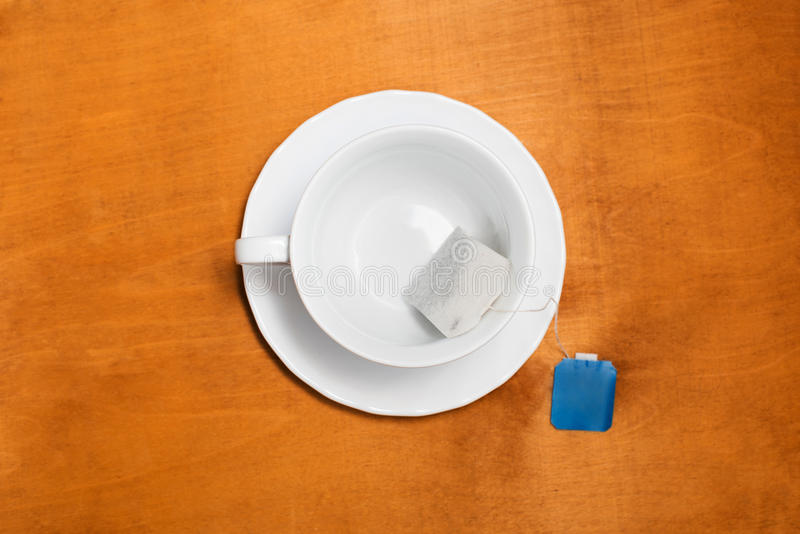 White cup with a tea bag with a blue label royalty free stock photo