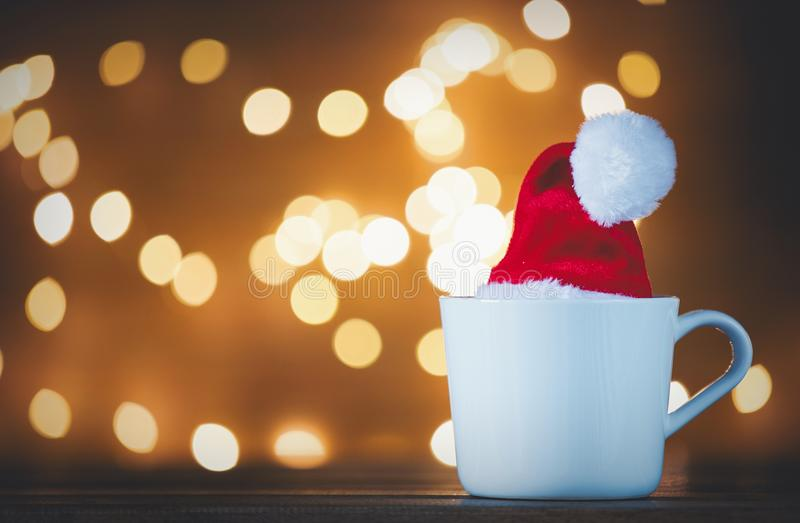 White cup of tea or coffee and Christmas Lights. On background royalty free stock photo