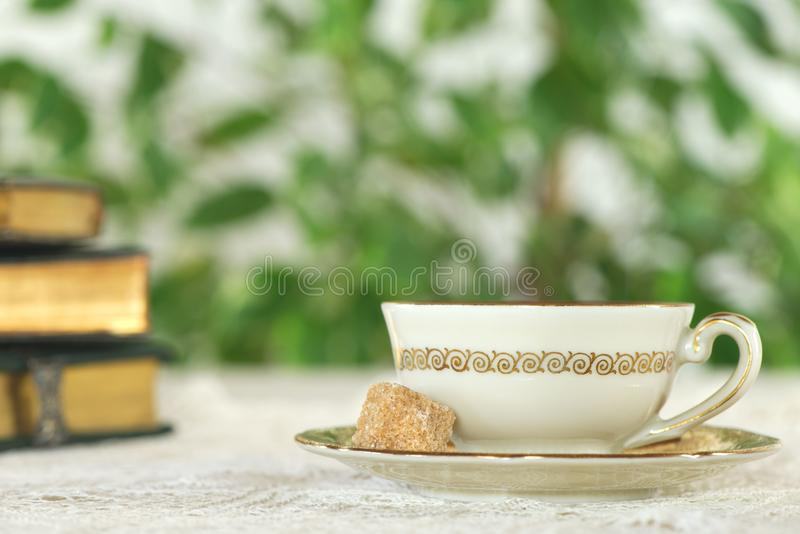 White cup of tea with golden books royalty free stock images