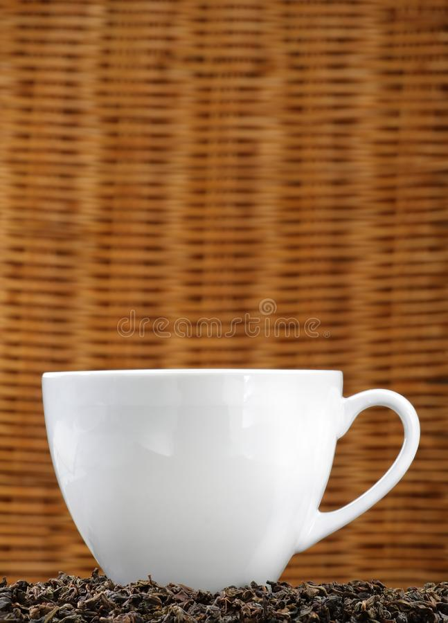 White cup on tea leaves royalty free stock photography