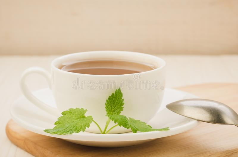 White cup of tea and leaves of mint in a saucer and spoon/white cup of tea and leaves of mint in a saucer and spoon on a wooden. Tray. selective focus green stock photos