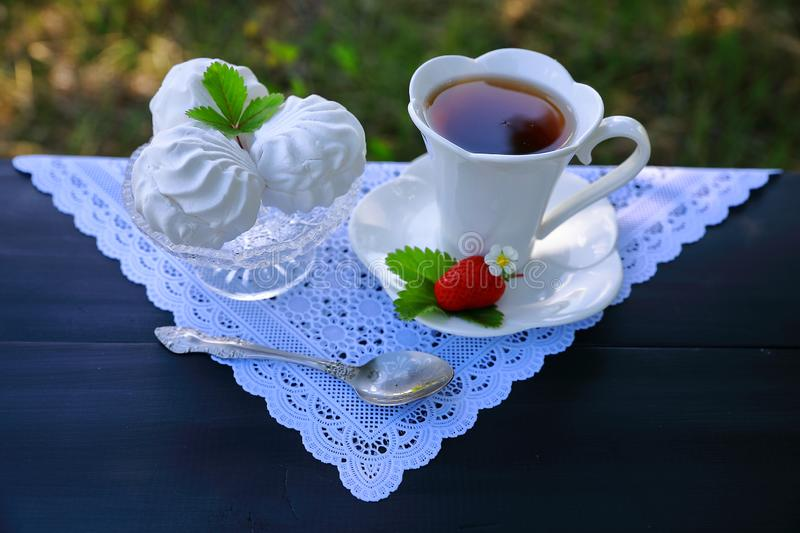 A white cup of tea, marshmallow and strawberry stock images
