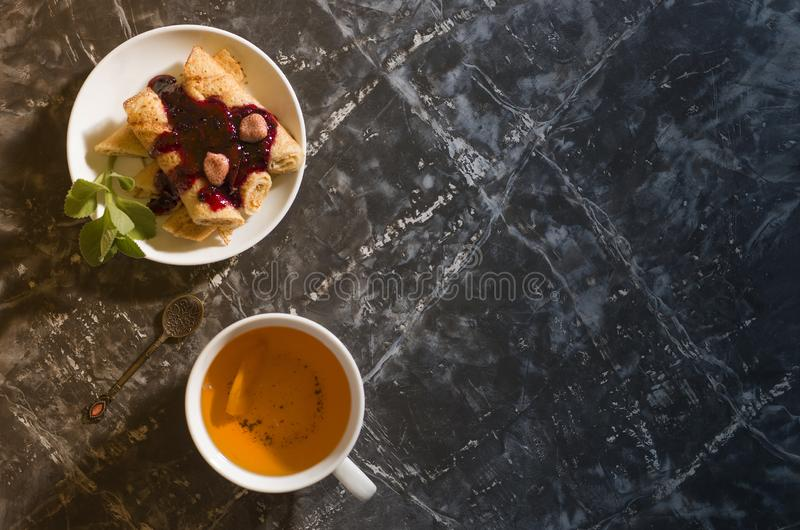 White cup with tea, pancakes with currant jam royalty free stock image