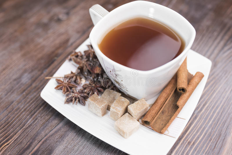 A white cup with tea, pieces of brown sugar, cinnamon sticks, anise stars lie on a white square saucer royalty free stock image