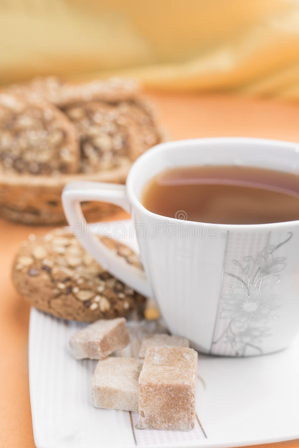 White cup with tea, pieces of brown sugar and homemade cookies with cereals on a white saucer stock images