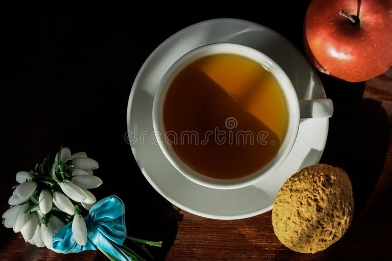 White cup with tea on a saucer with oatmeal cookies and red apple and a small bouquet of snowdrops tied with a blue ribbon stock image