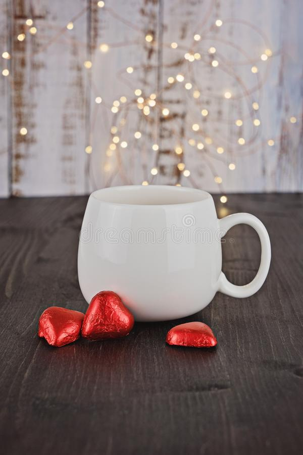 White cup with Valentine chocolate candy red hearts royalty free stock photography