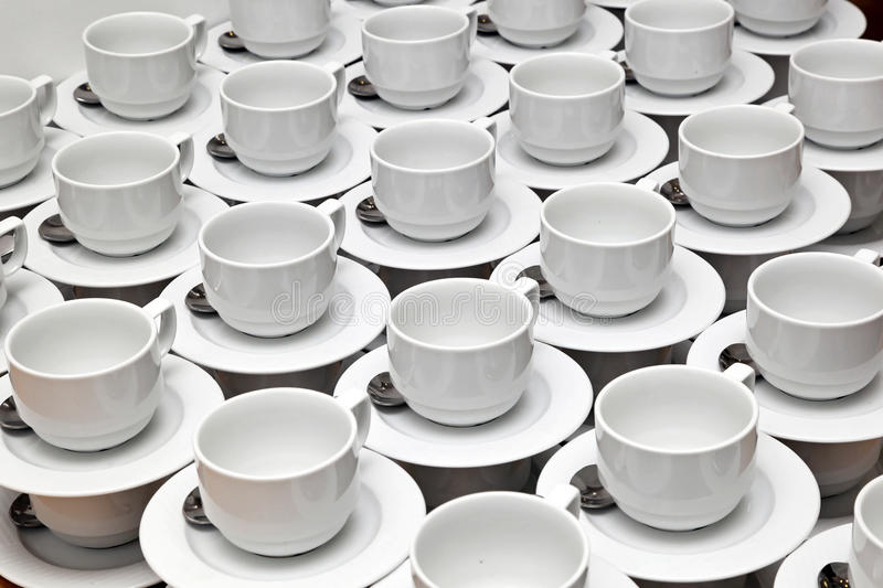 White cups. Big bunch of plain white ceramic cups stock image