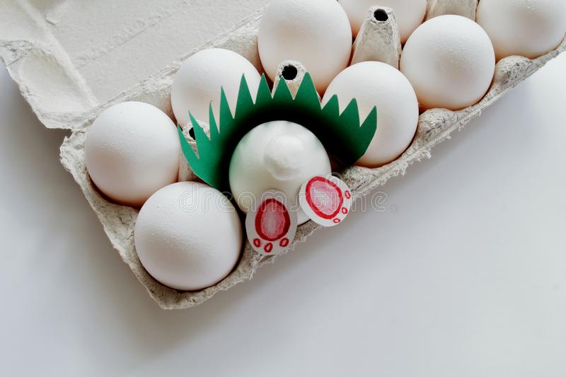 White curious homemade Easter bunny in carton among the eggs on white background. Easter concept royalty free stock photo