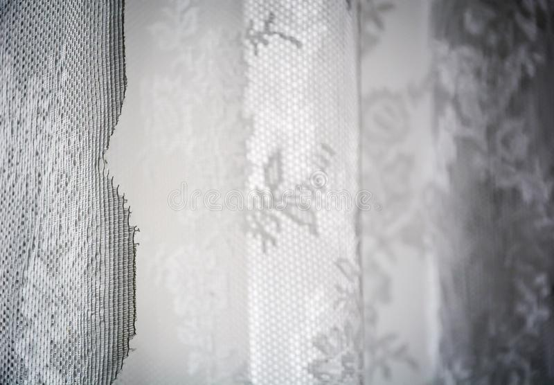 White curtain decorated with sewed floral pattern in lace. Interior shot with natural soft light royalty free stock image